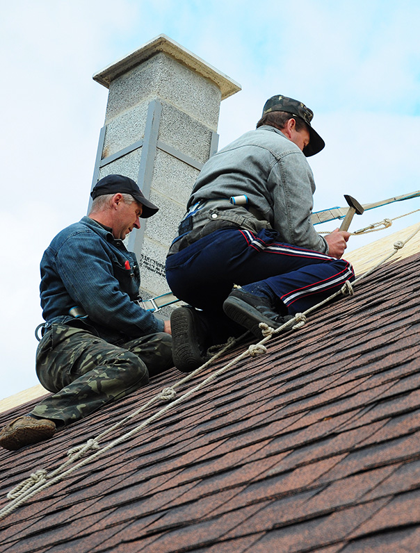 Roofing Construction. Roofing Contractors Install New House Roofing with Asphalt Shingles Roofing Construction. Roofers with safety rope. Roofing Contractor.