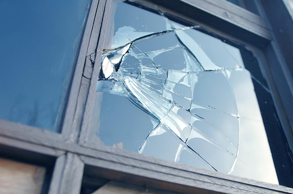 broken glass window in wooden frame reflecting blue sky