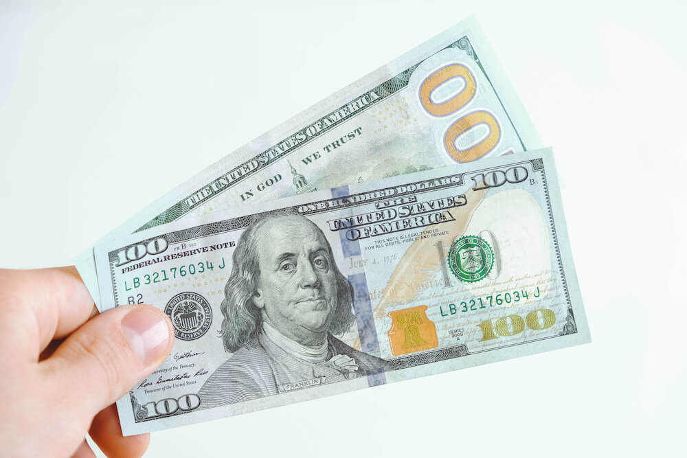 Two Hundred Dollar Bills In Hand On A White Background