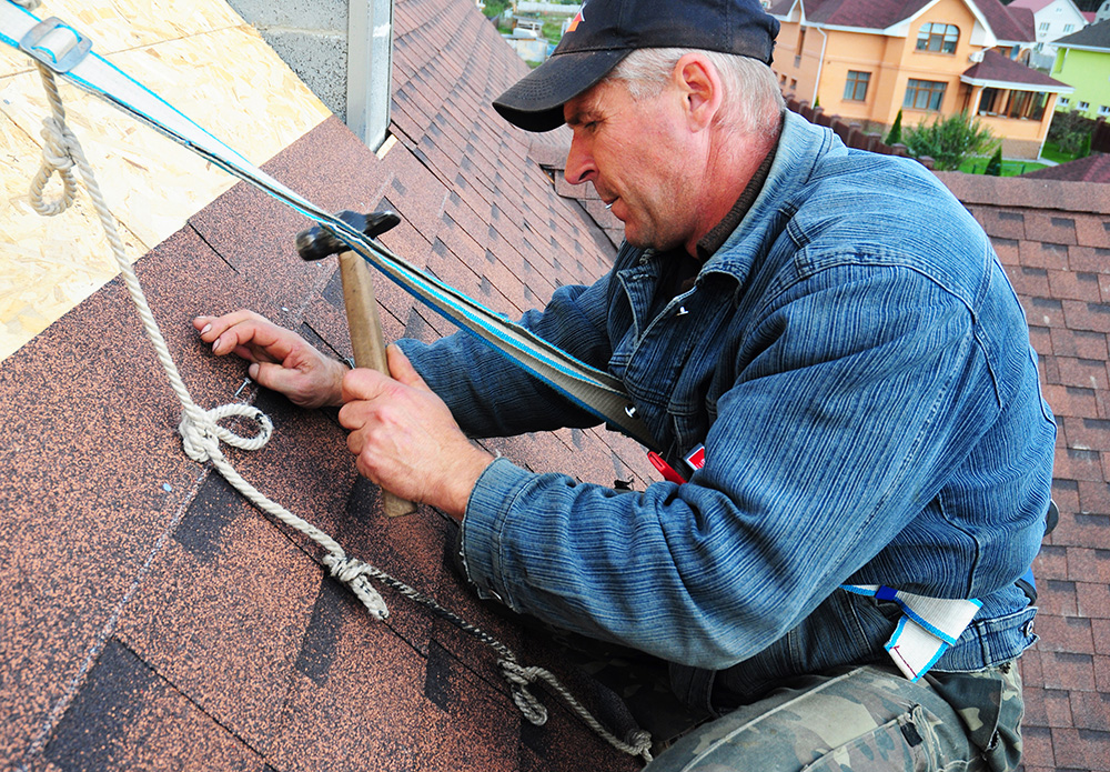 Asphalt roofing contractor laying asphalt shingles on house rooftop. Roofer repair asphalt roofing shingles
