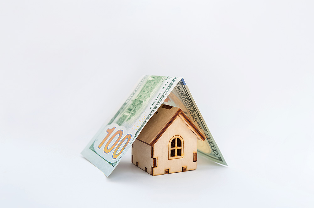 A miniature house and a banknote like a roof to convey roof financing