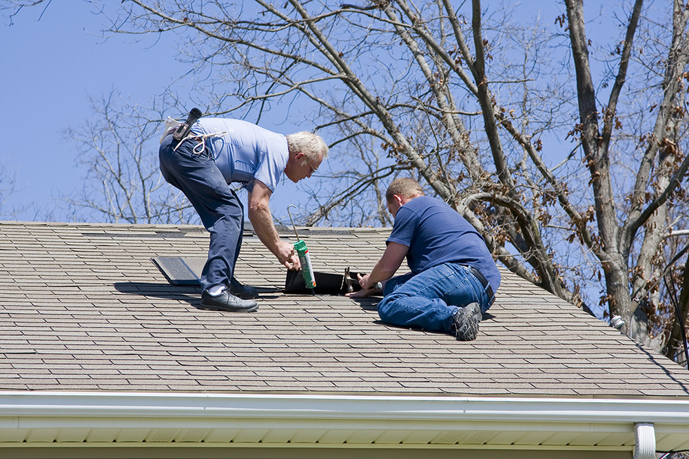 Roofing contractor repairing damaged roof on home after recent wind storms many roofs were damaged