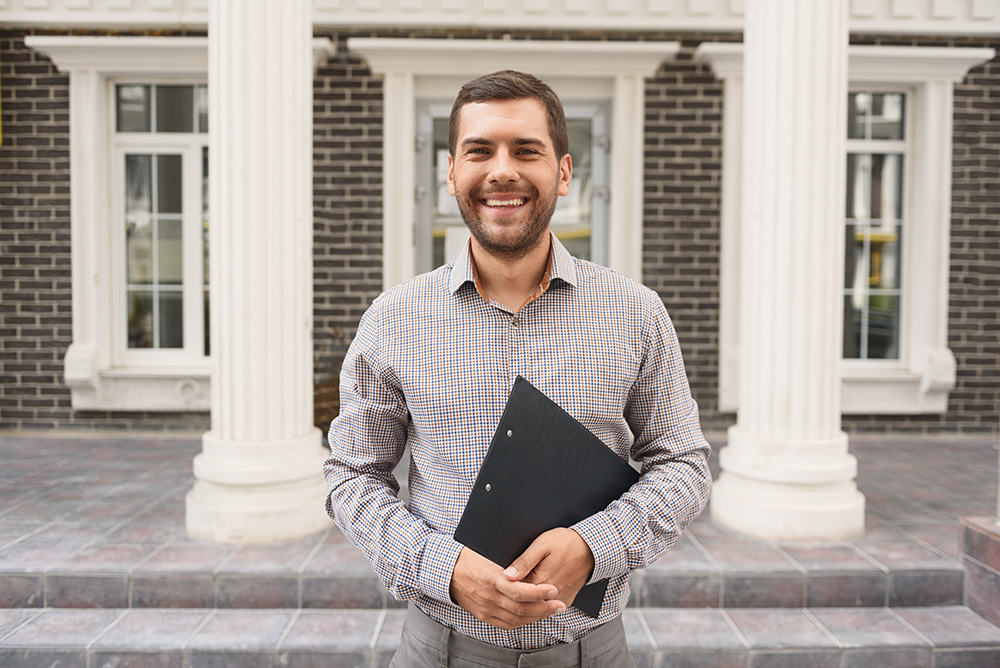 Pleasant cheerful handsome roof estimator holding estimate and expressing positivity while standing outside