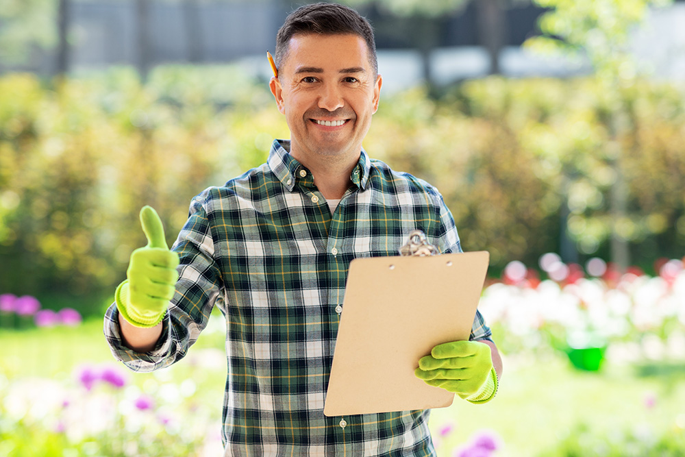 Happy smiling middle-aged man with clipboard showing thumbs up
