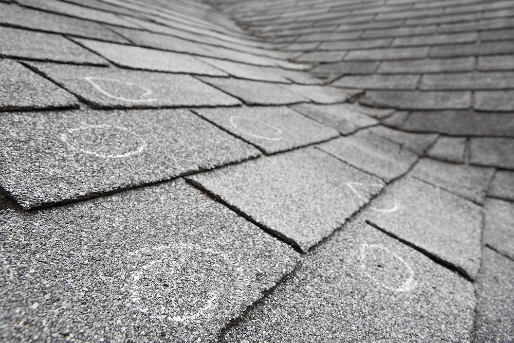 Old roof with hail damage, chalk circles mark the damage.