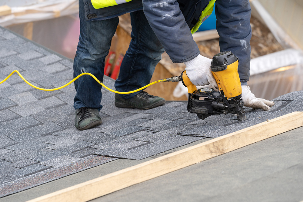 Close up photo of professional roofer worker in uniform work wear using air or pneumatic nail gun and installing asphalt shingles on top of the new roof under construction