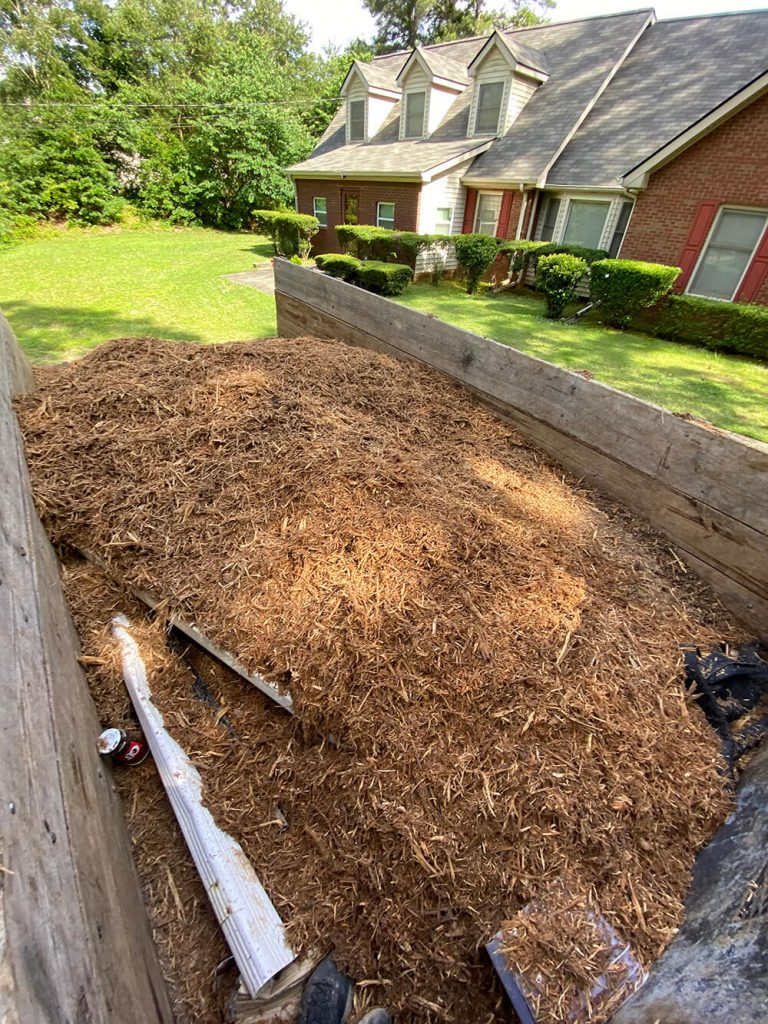 Trailed filled with mulch and wood chips in front of home with new roof