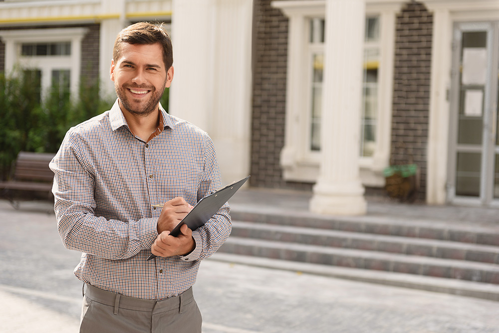 Roof inspector standing outside residential property, holding clipboard and smiling