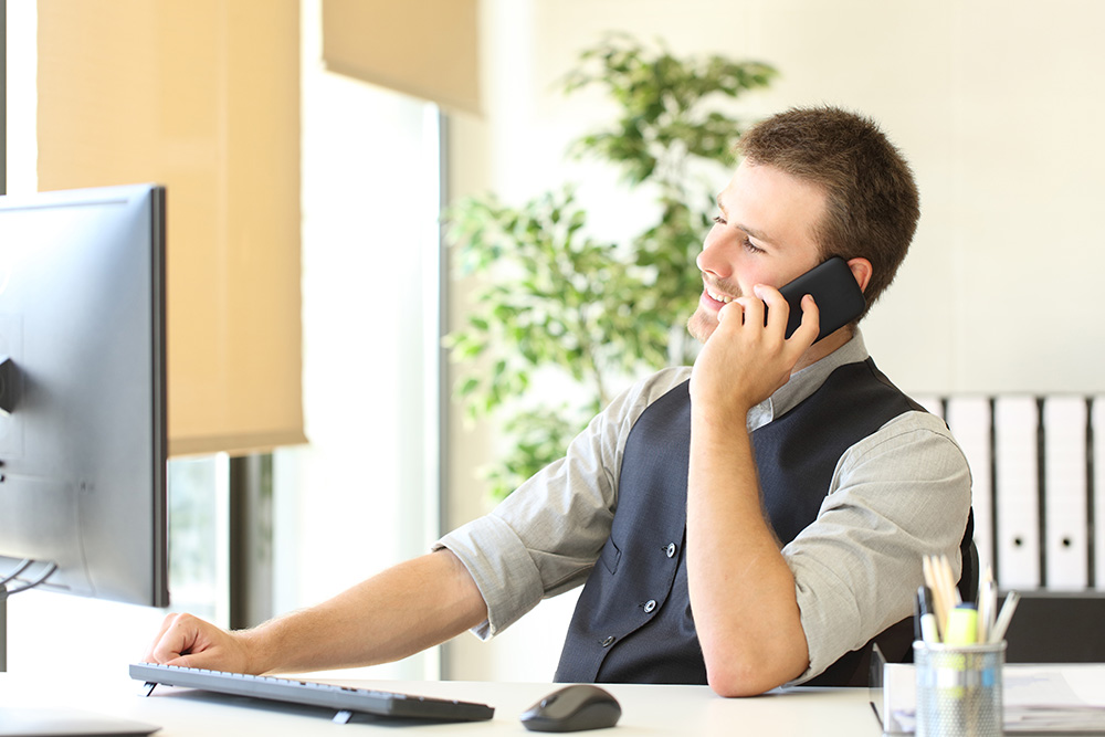 Happy person is talking on phone looking away at office
