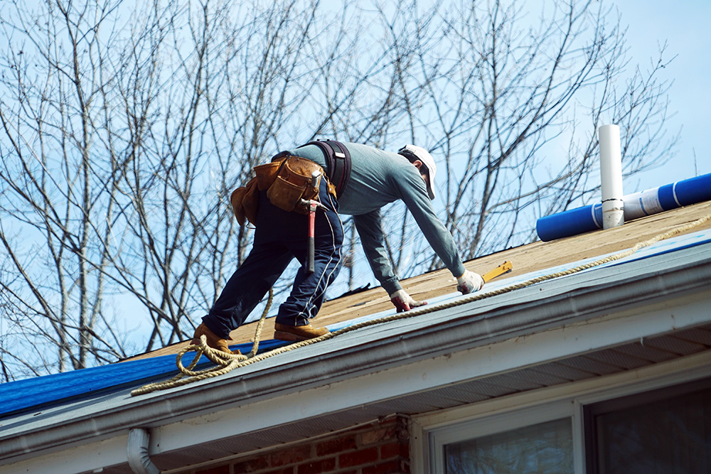 Handyman working on repairing the roof for design