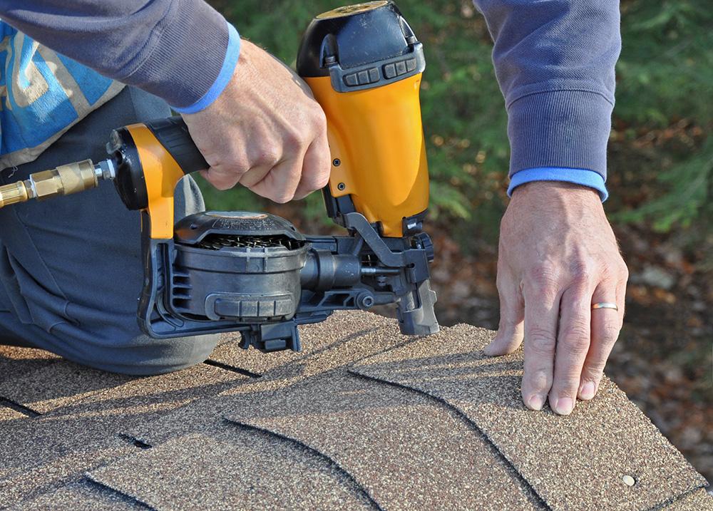 Man using nail gun to attach asphalt shingles to roof
