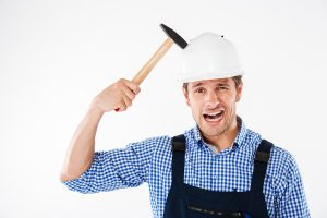 Smiling funny young builder applying hammer to his head in helmet and having fun isolated on a white background